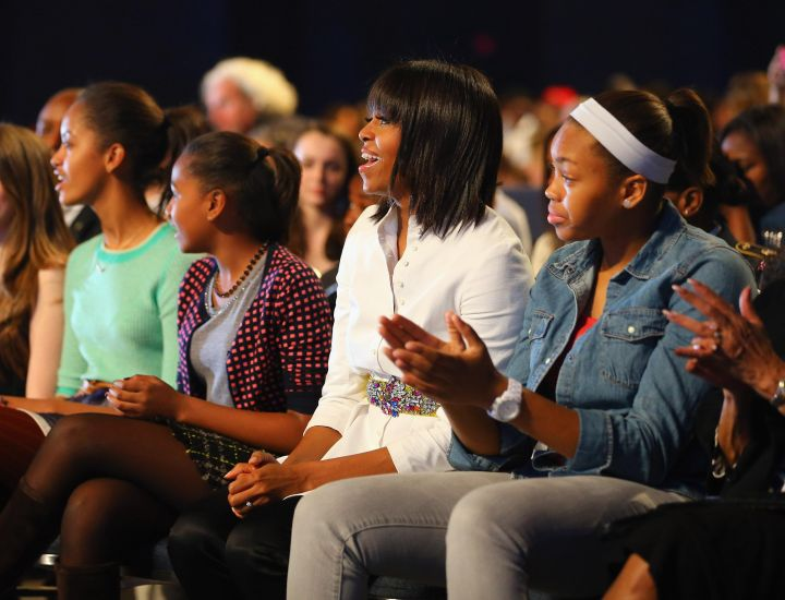 First Lady Michelle Obama watches the show with her daughters Malia and Sasha