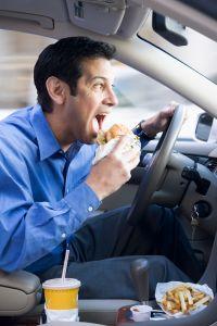 Hispanic businessman eating and driving