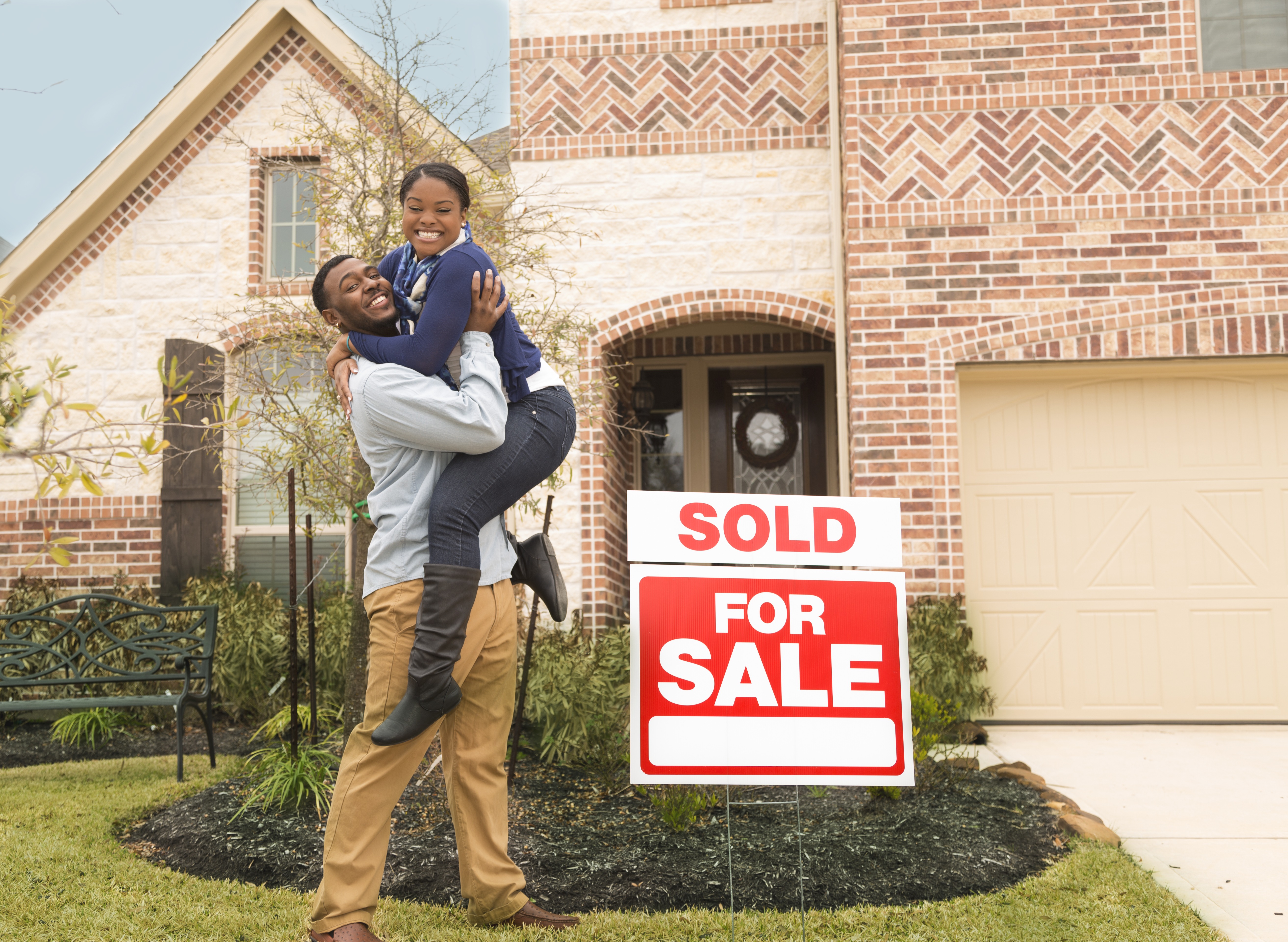 Excited couple jumps for joy in front of first home.