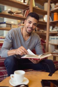 Smiling African American student enjoying book reading in library