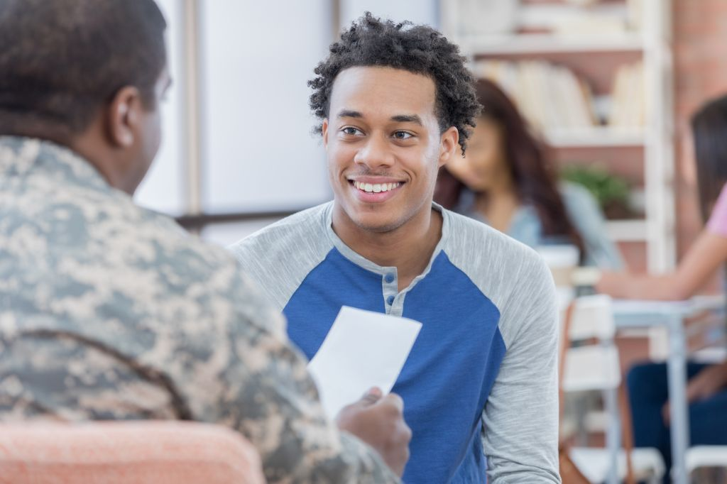 Smiling young man talks with military officer