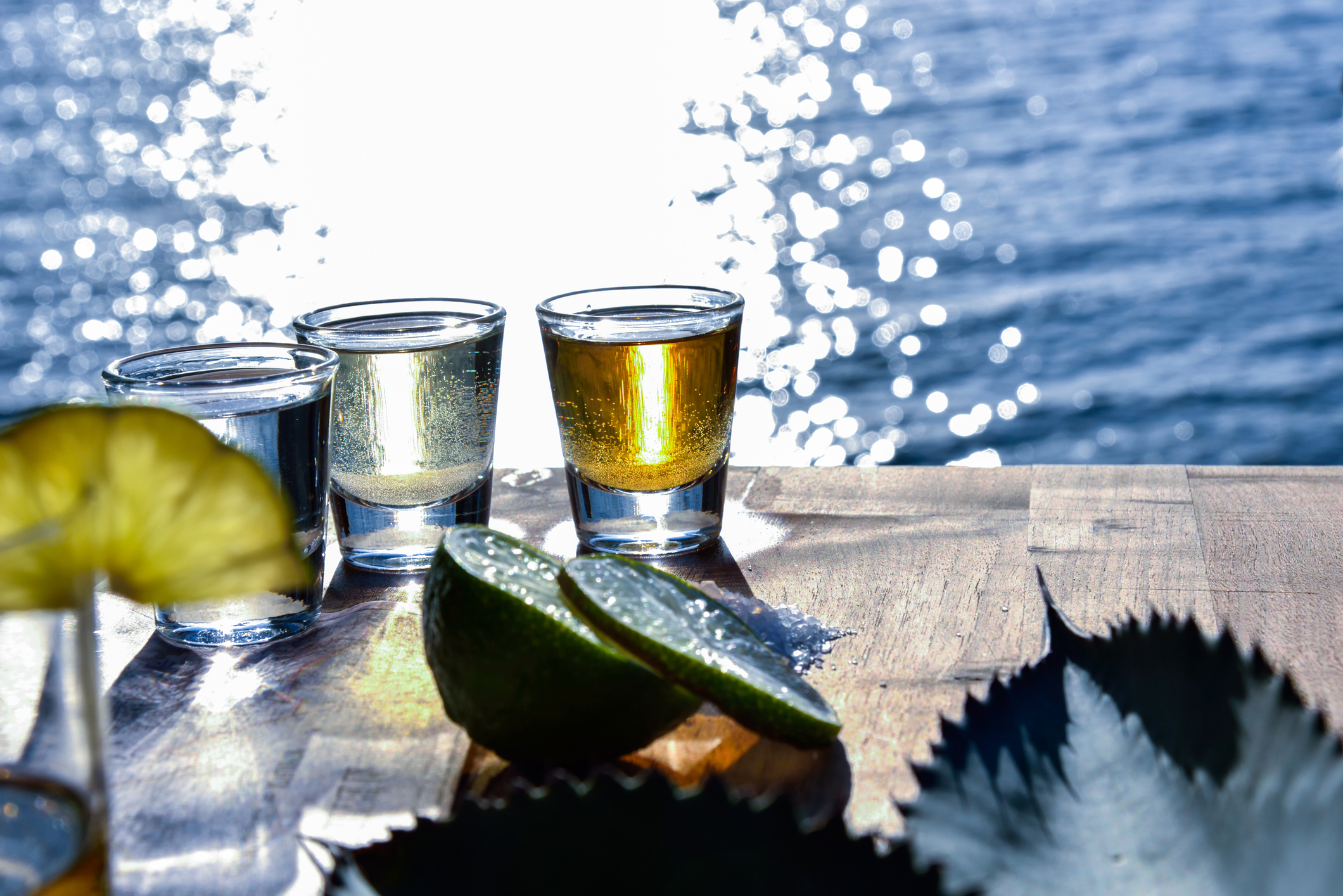 Close-Up Of Tequila Shots With Lemon On Table By Sea