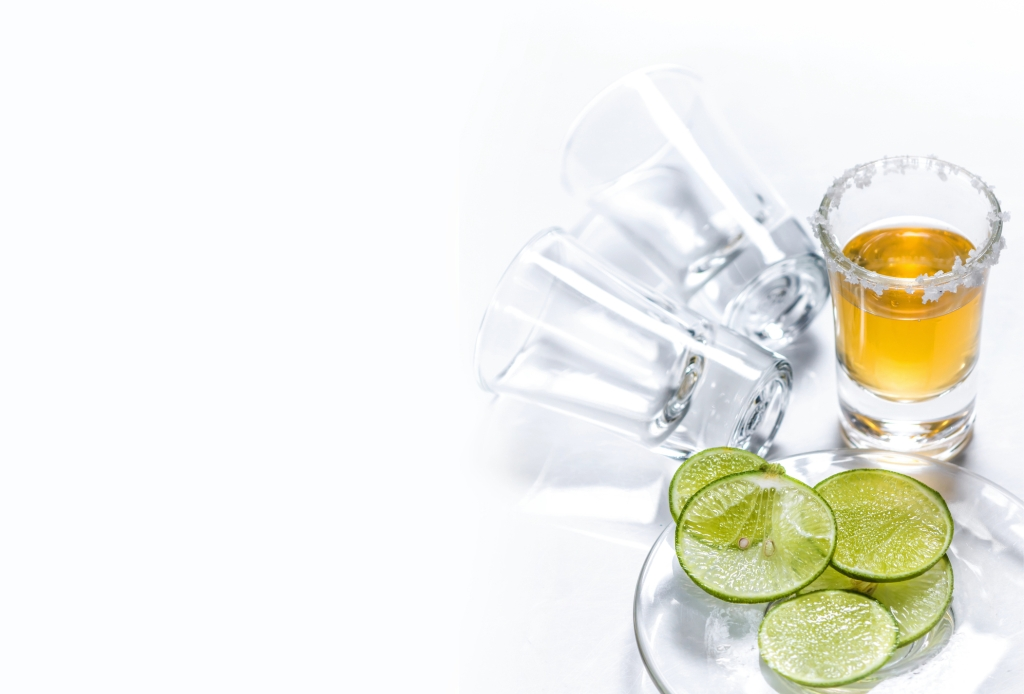 High Angle View Of Tequila Shot By Lime Slices On White Background