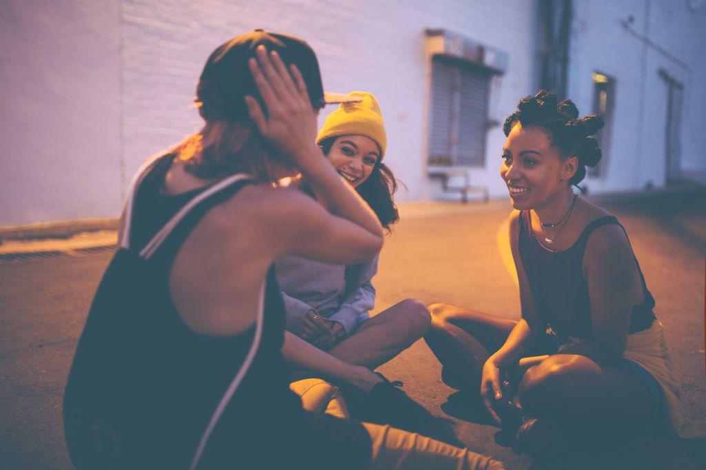 Teen girls sitting on street at night talking and laughing