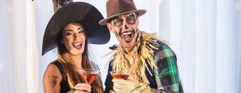 Witch and scarecrow at adult halloween party