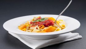 Dish of rigatoni pasta topped with tomato concasse