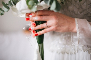 Bride holding wedding bouquet with wedding ring on her hand