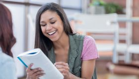Smiling college student reads a book with her friend