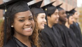 Educaton: African descent graduate and friends on college campus.
