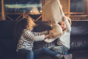 Playful black kids having fun while fighting with pillows at home.
