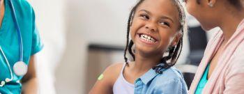 Smiling girl receives immunization from nurse