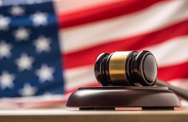 Judges wooden hammer in front USA flag.
